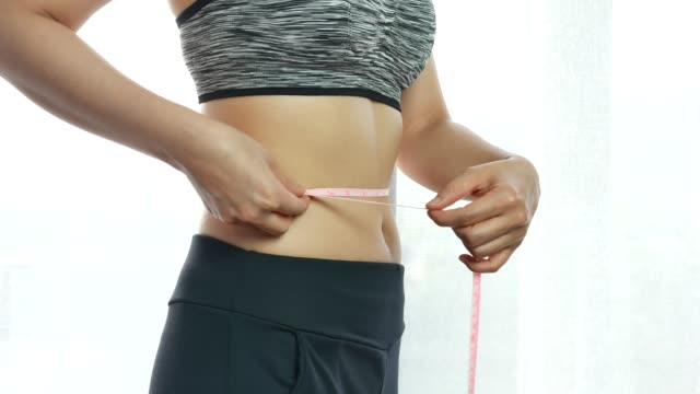 Measuring waistline of a beautiful body in inches Measuring waistline of a beautiful body in inches weight loss stock videos & royalty-free footage