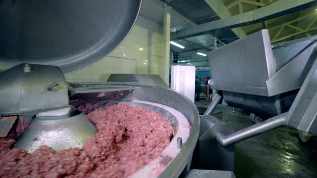 Meat being minced at a plant. Special equipment lifts minced meat and throws it into a big container. ground beef stock videos & royalty-free footage