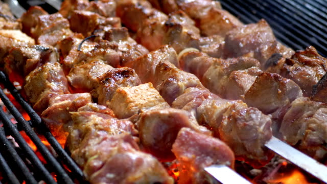 meat grilled on skewers on the grill on the street market - spiedino video stock e b–roll