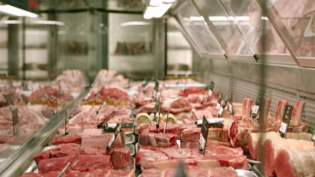 Meat in a butcher's shop Various cuts of steak and beef on display at a Butcher's shop beef stock videos & royalty-free footage