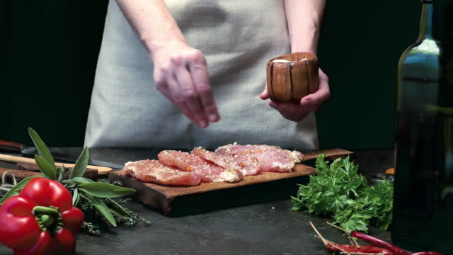 Meat loin cooking Woman cooking meat loin. Adding salt to raw pork. Fresh vegetable and seasoning on foreground. Black background. Midsection view pork stock videos & royalty-free footage