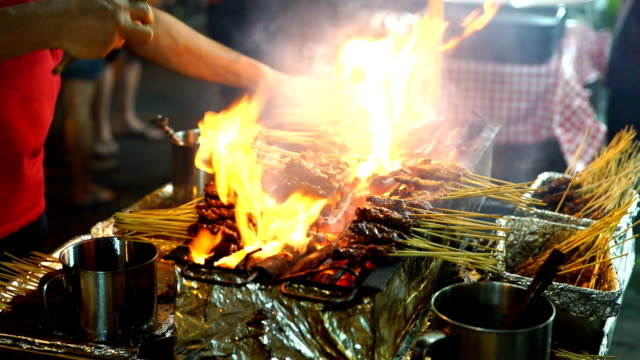 meat skewers cook over hot coals in singapore's satay street food market - malese video stock e b–roll