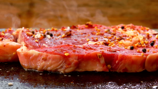 vídeos de stock e filmes b-roll de meat sprinkled with pepper and spices is frying on the stone grill - beef angus