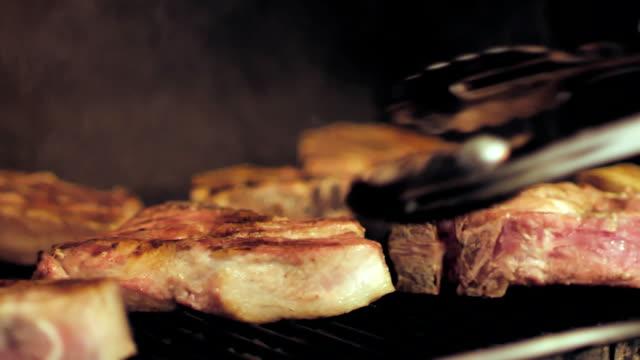 vídeos y material grabado en eventos de stock de filetes de carne son ser frito en una parrilla - pinzas utensilio para servir