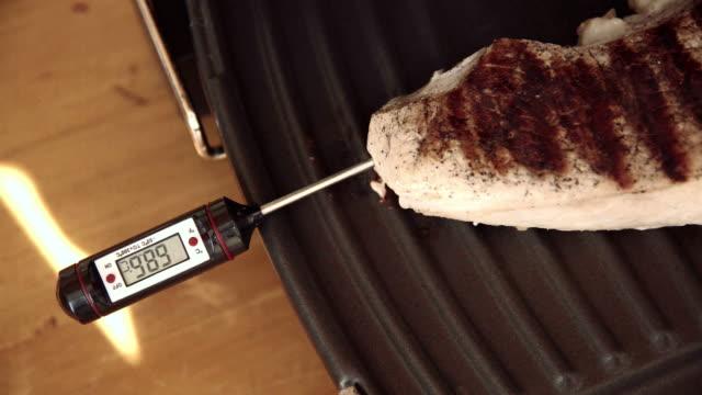stockvideo's en b-roll-footage met de thermometer van het vlees in biefstuk geplaatst op elektrische grill - thermometer