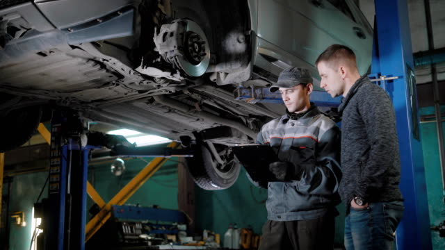 Mechanic and client are discussing the cost of the repair video