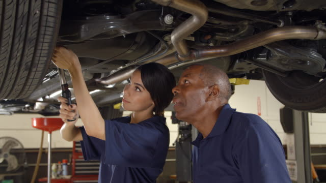 Mechanic And Female Trainee Working Underneath Car Together video