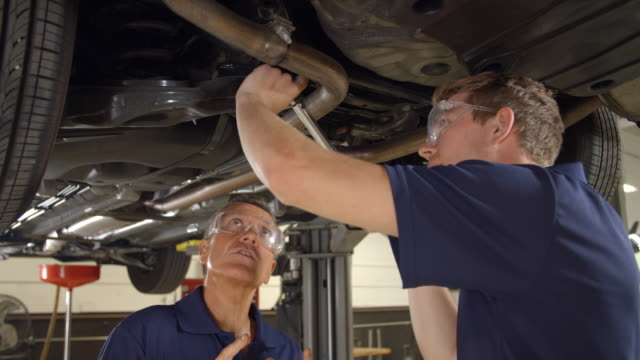 Mechanic And Male Trainee Working Underneath Car Together video