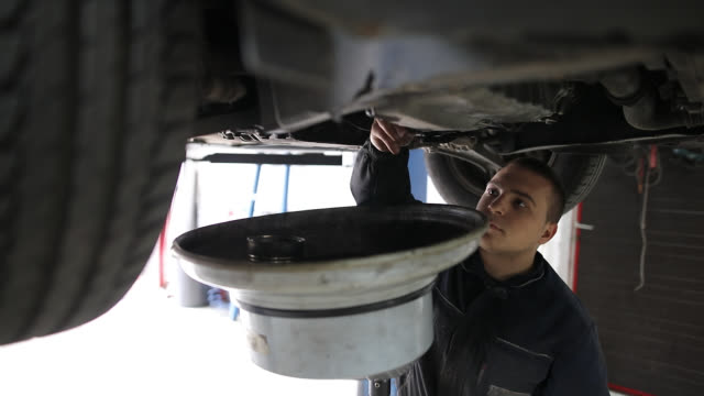 Mechanic changes engine oil in auto repair shop video