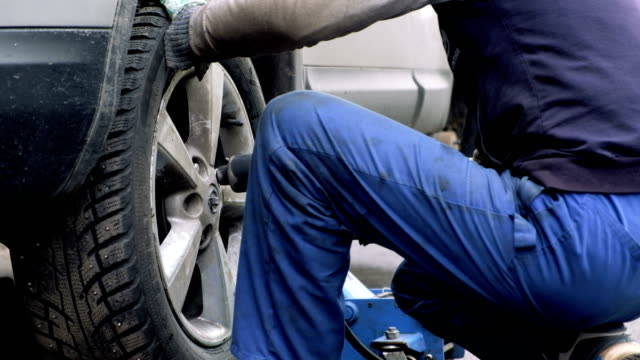 Mechanic changes the winter tires in the car video