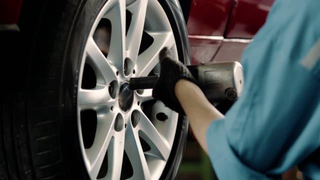 Mécanicien changeant le pneu à l'atelier de réparation automatique - Vidéo