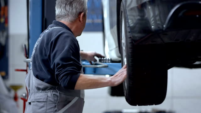 stockvideo's en b-roll-footage met mechanic changing the tire - werkplaats