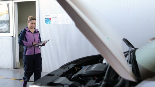 Mechanic diagnostic, checking results on laptop in garage