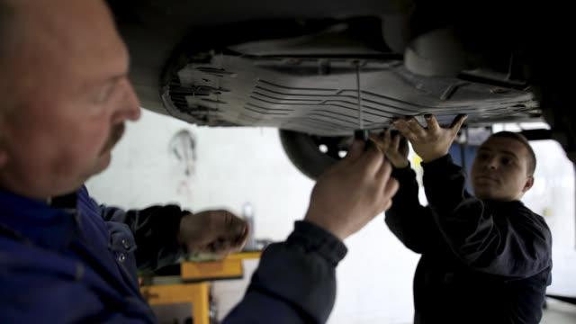 mechanic examining undercarriage at auto repair shop - часть машины стоковые видео и кадры b-roll