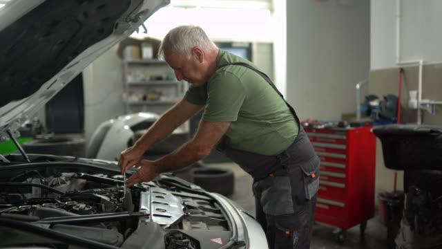 Mechanic examining vehicle hood at auto repair shop Mechanic examining vehicle hood at auto repair shop vehicle part stock videos & royalty-free footage