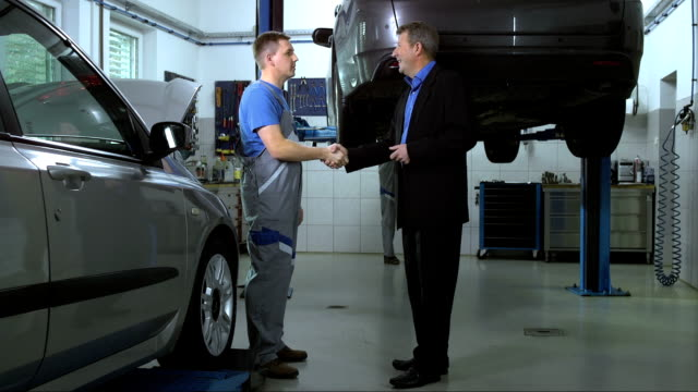stockvideo's en b-roll-footage met mechanic explaining repairs to customer - werkplaats
