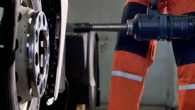 mechanic fasten the tire with pneumatic screwdriver - mechanic video stock e b–roll