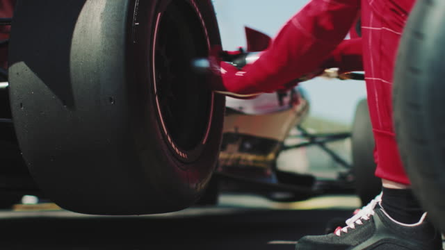 mechanic fastening tire of racecar at pit stop - rack focus video stock e b–roll