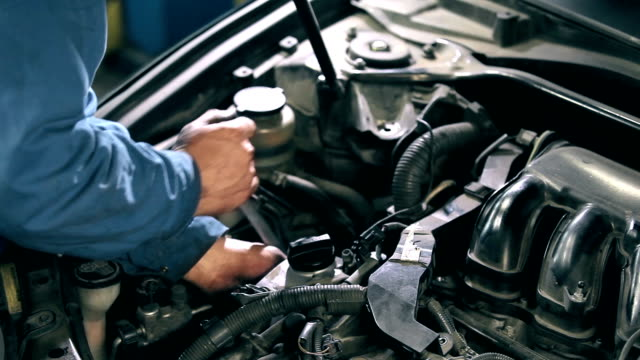 Mechanic fastens detail of car engine video