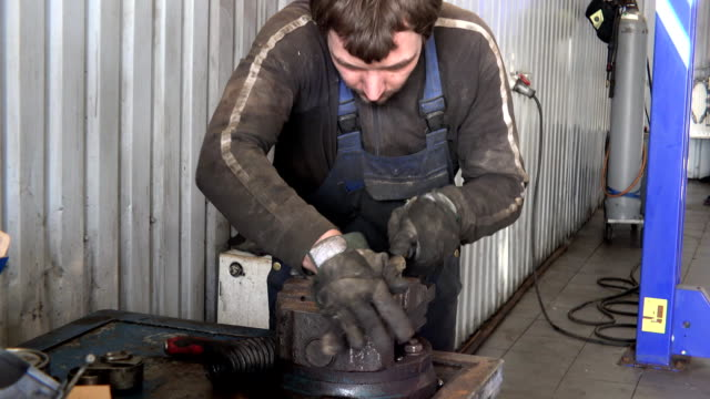 mechanic guy grind rusty metal with rasp tool in garage. video