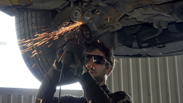 mechanic guy with glasses cutting worn automobile part with grinder in garage - rettificatrice video stock e b–roll