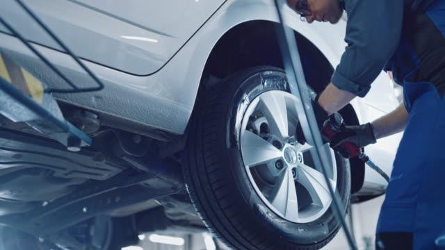mekaniker i blue overaller är skruva lug nötter med en pneumatisk impact wrench. reparatör arbetar i en modern ren bilservice. specialister tar bort hjulet för att fixera en komponent på ett fordon. - garage bildbanksvideor och videomaterial från bakom kulisserna