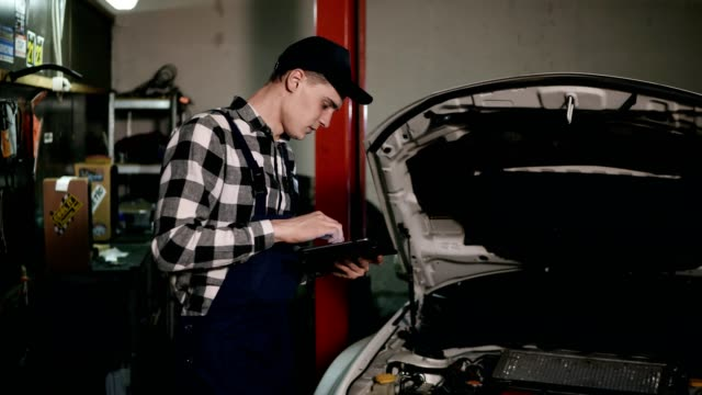 Mechanic inspects the car undercarriage way with a digital tablet video