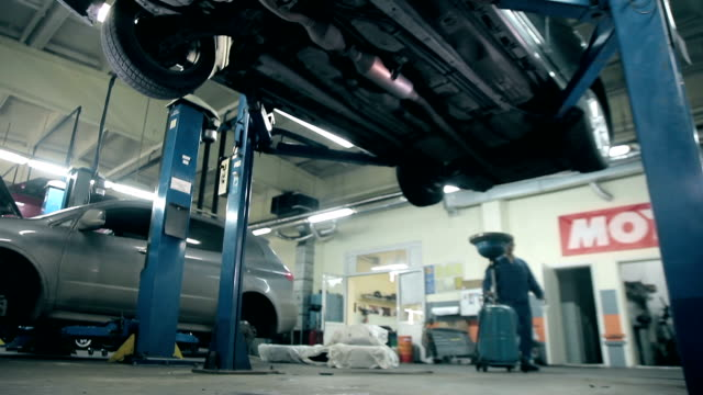 Mechanic is going to drain engine oil from a car video