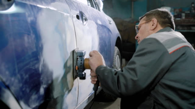 mechanic is preparing automobile for painting - rettificatrice video stock e b–roll
