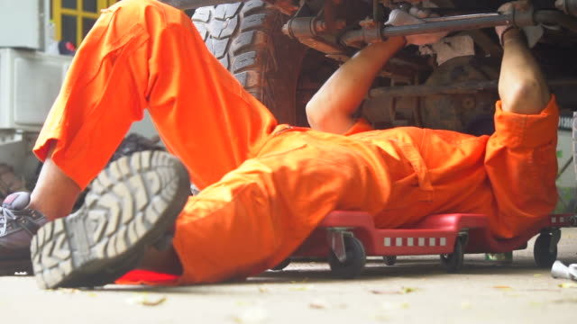 mechanic laying down and move to under vehicle - sotto video stock e b–roll
