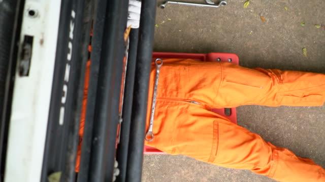 mechanic laying down and move to under vehicle - mechanik filmów i materiałów b-roll