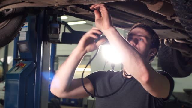 Mechanic listen engine with stethoscope in repair garage video