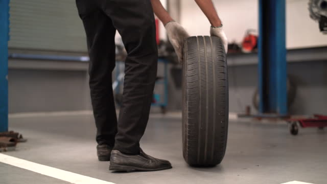 vídeos de stock e filmes b-roll de mechanic man change a wheel tire and service maintenance the suspension of a vehicle , safety inspection test engine before customer drive a car on a long journey, transportation service - gmail