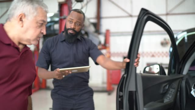 Mechanic man explaining to his customer the defect of his car in a repair shop