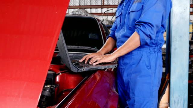 メカニック男はノート パソコンを使用して車をチェックします。車のサービス、修理およびメンテナンスの概念を持つ人々。 - 機械工点の映像素材/bロール