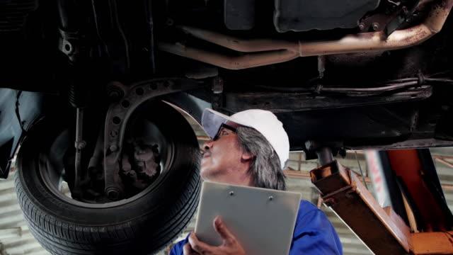 ワーク ショップ車のサービス、修理、保守および人々 のコンセプトで働いていたメカニックの男性。 ビデオ