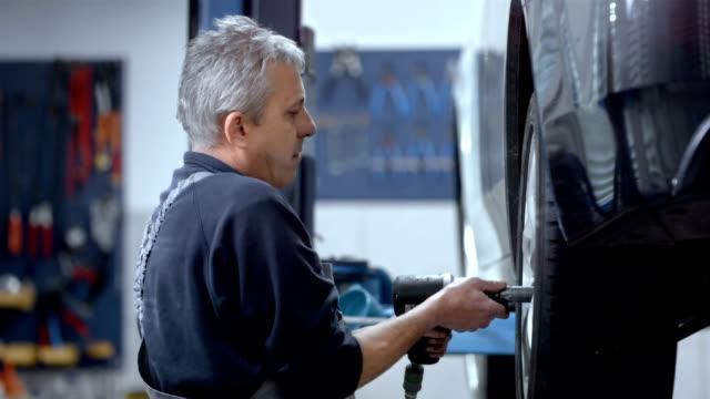 mechaniker aufziehen ein auto-rad - werkstatt stock-videos und b-roll-filmmaterial