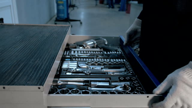 mechanic open blue metal box with different tools for car repair at modern service station - pinze attrezzo manuale video stock e b–roll