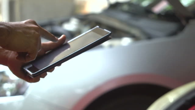 meccanico che revisiona un'auto in tablet - garage video stock e b–roll