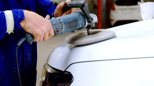 mechanic polishing a car with grinder 4k - lucidare video stock e b–roll