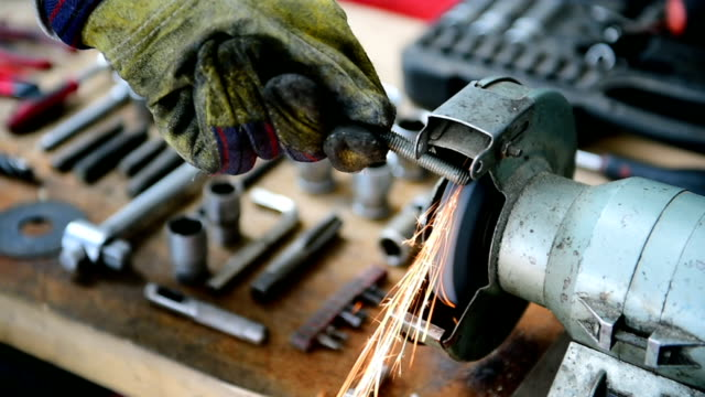 Mechanic polishing a screw on industrial polishing machine video