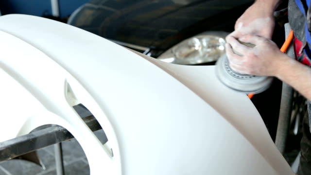 mechanic prepares the car body of the car for painting. grinding the car body. - lucidare video stock e b–roll