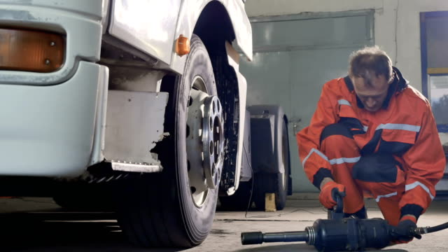 Mechanic preparing to unscrew the tire with screwdriver video