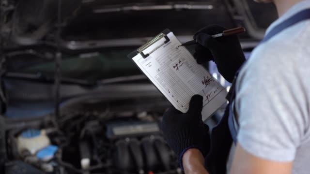 mechanic repairman inspecting car - ispettore della qualità video stock e b–roll