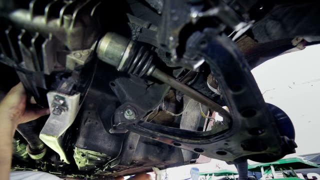 Mechanic repairs a car from bottom of the chassis video