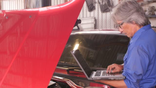 メカニックは、車サービス、車のサービス コンセプトのフードの下で pc を使用して損傷を修復します。ドーリー ショット - 機械工点の映像素材/bロール