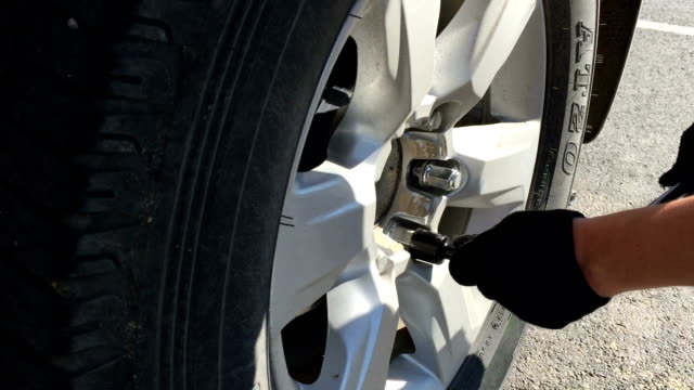 mechanic screwing or unscrewing changing car wheel by wrench - klucz ręczne narzędzie filmów i materiałów b-roll