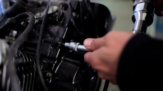 Mechanic screws in the bolt by the electric wrench video