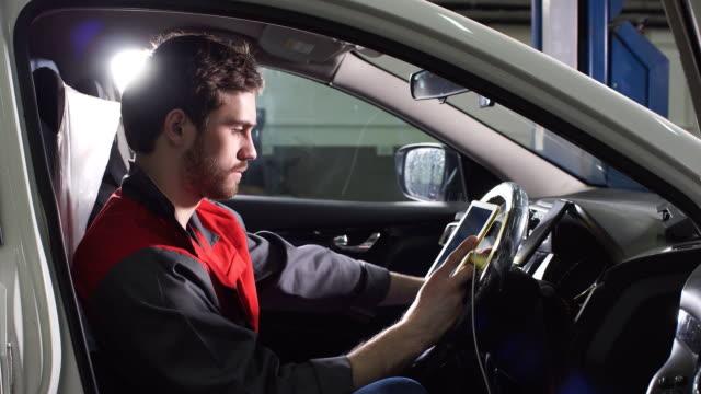 Mechanic sitting in car doing diagnostics on digital tablet video