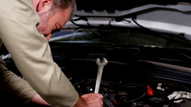 Mechanic standing with arms crossed while servicing a car engine Portrait of mechanic standing with arms crossed while servicing a car engine at repair shop 4k wrench stock videos & royalty-free footage